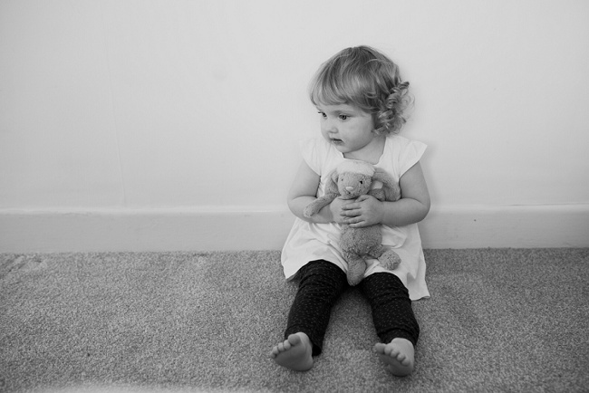 little girl sitting with toy rabbit
