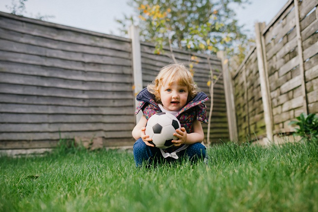 little girl in grass with football