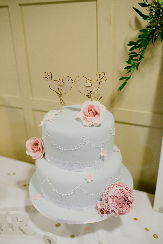 pale blue wedding cake with bird topper