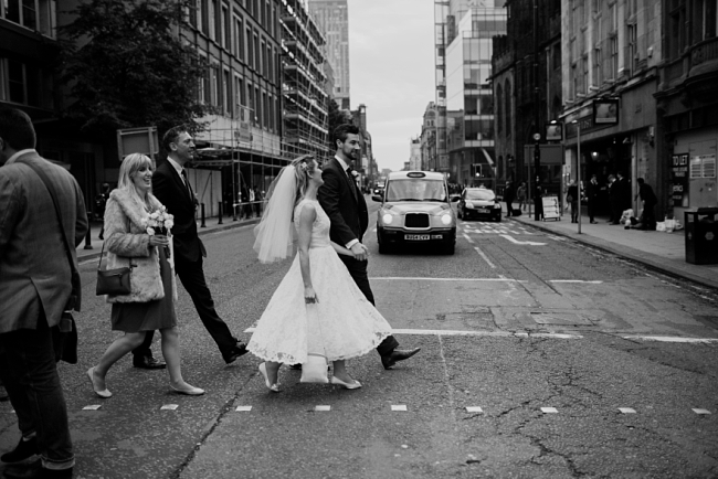 bride and groom crossing road in manchester