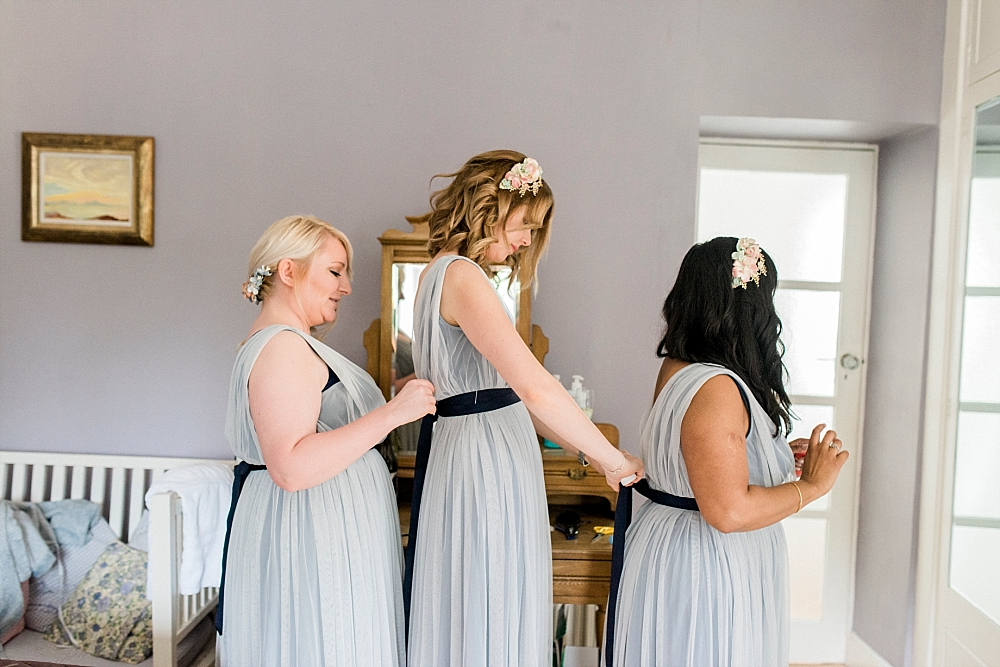 bridesmaids tying dresses
