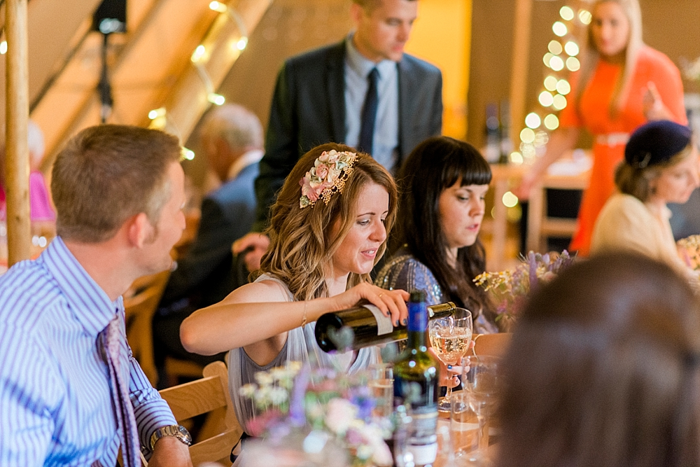 bridesmaid pours wine