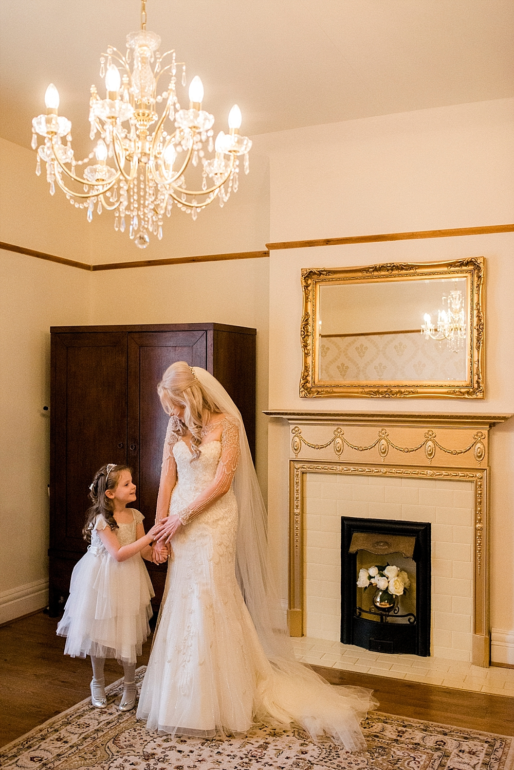 blonde bride in vintage style beaded dress with flower girl under chandelier