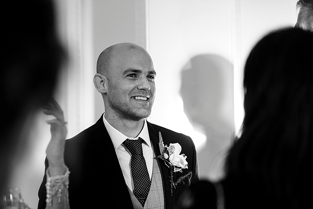 black and white photo of groom smiling in a crowd