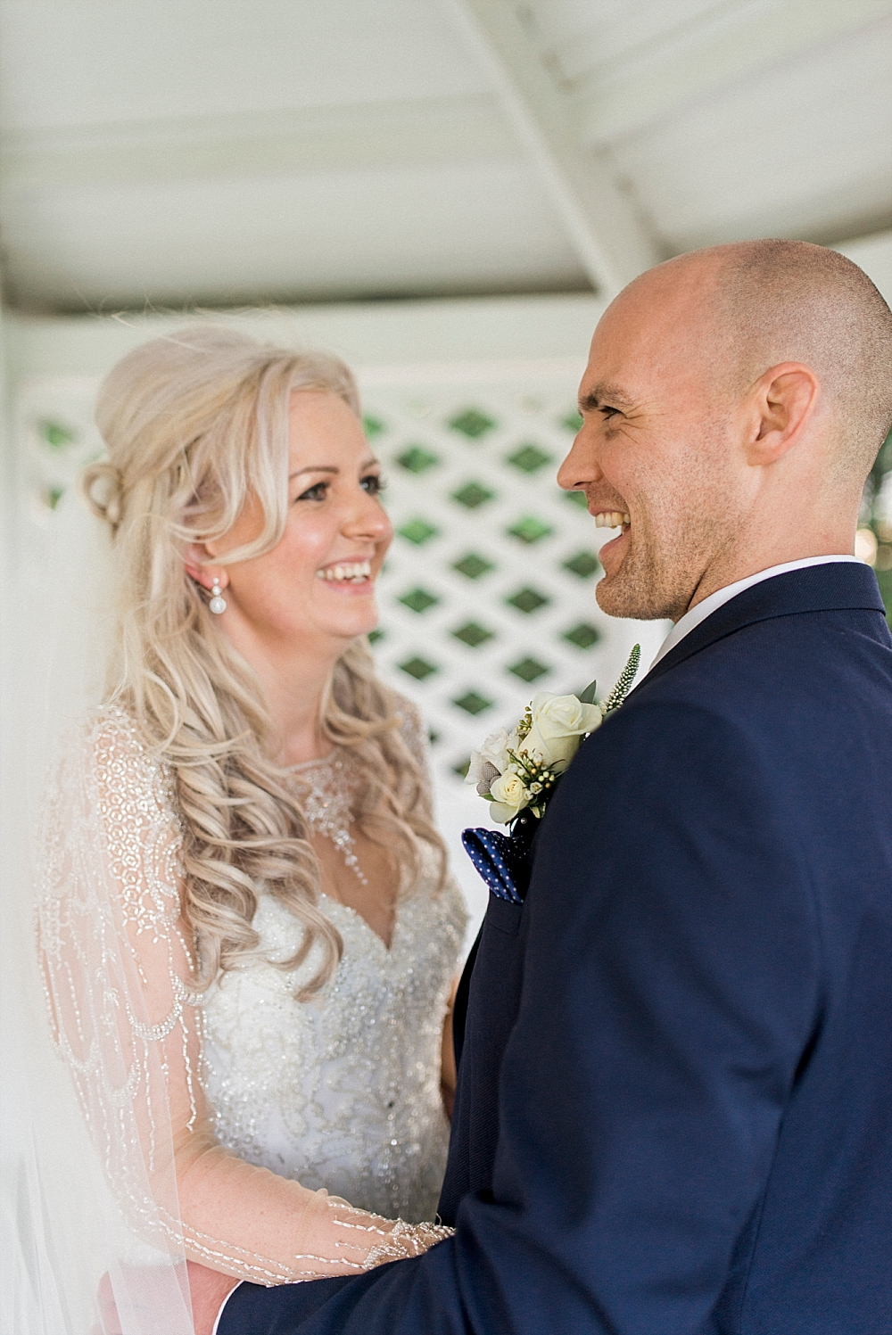 blonde haired bride and her groom laughing under pergola at west tower