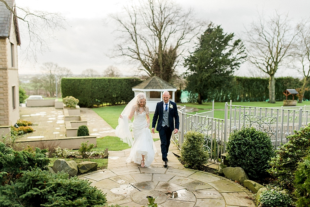 bride and groom walking in the garden at west tower in winter