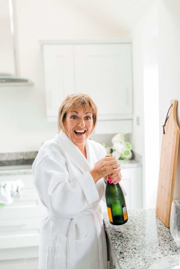 mother of bride opens champagne