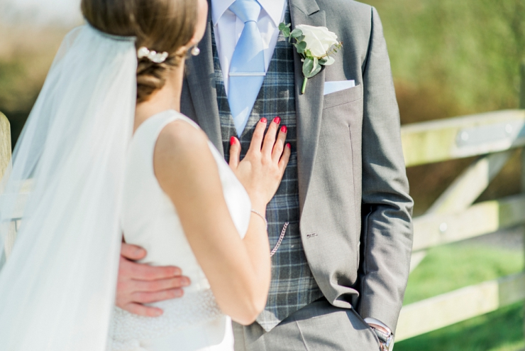 groom in grey suit bride with red nails