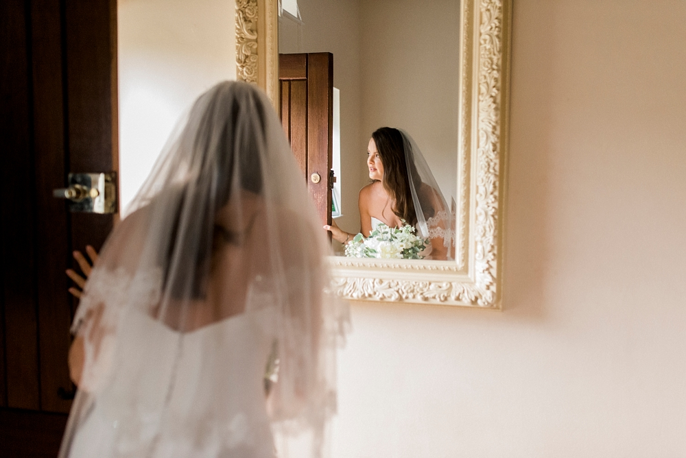 bride ready to leave peepes out of front door with reflection in mirror
