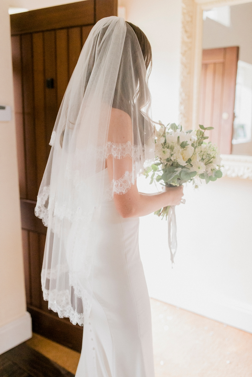 bride with lace veil and simple, classic dress