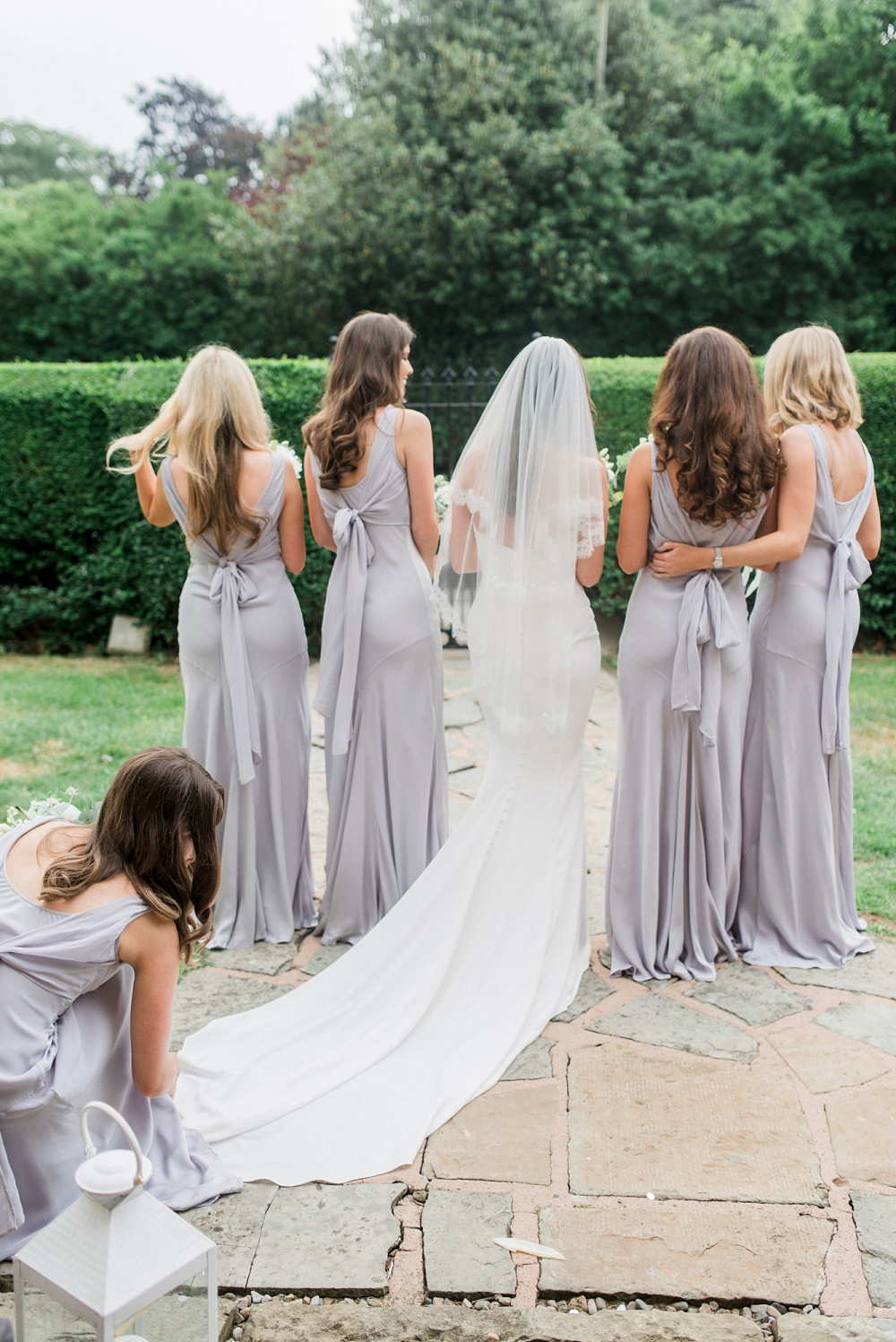 bridesmaid adjusts brides train