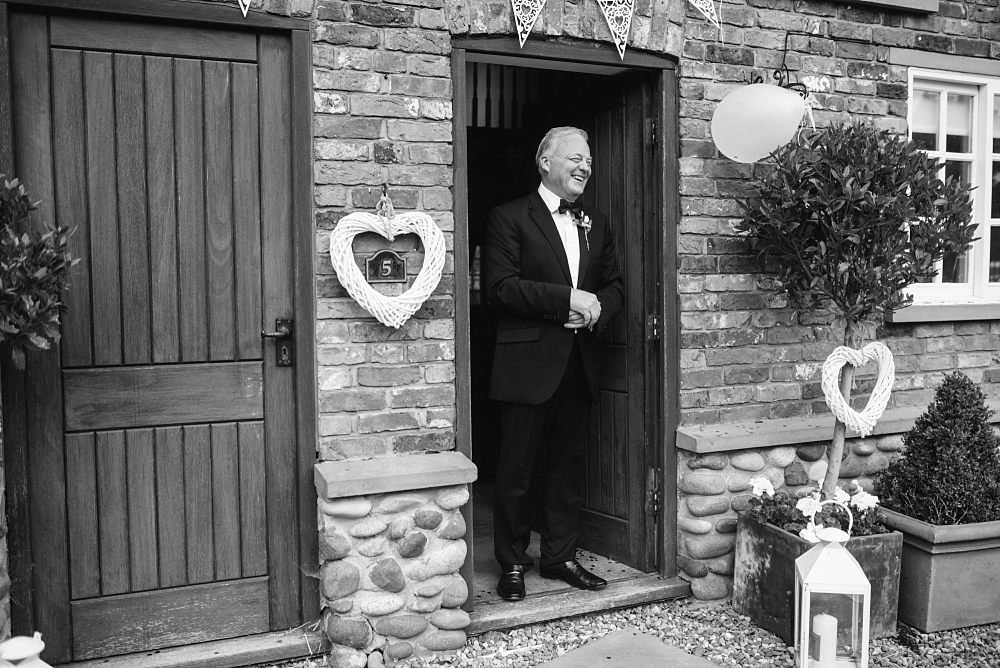 father of the bride laughs in doorway