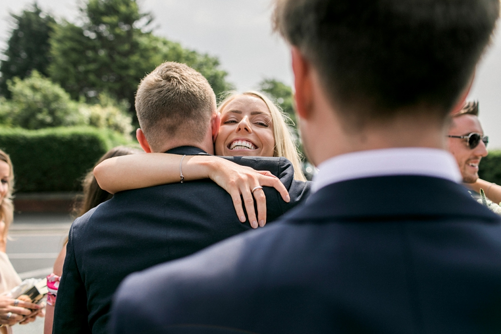 bridesmaid hugging groomsman