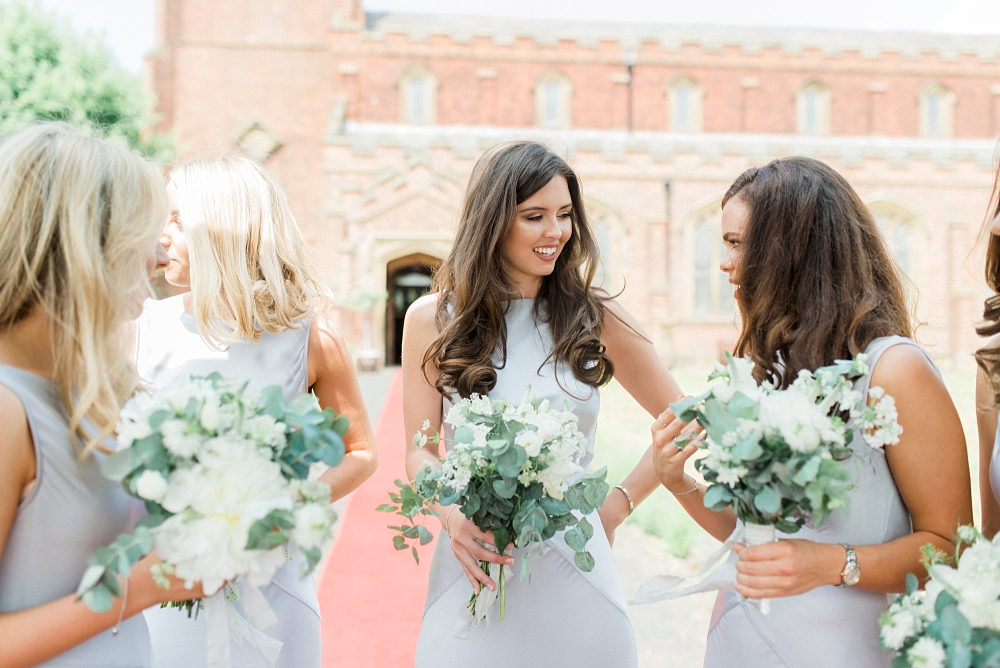 bridesmaids with bouquets in the sunshine outside church