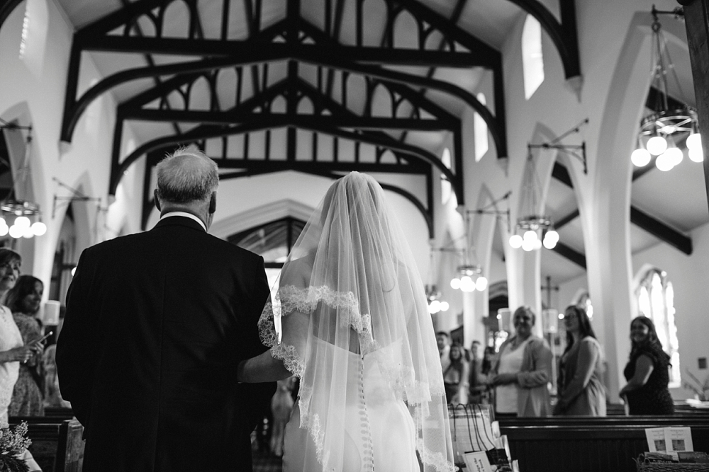 bride and her dad walking down the aisle photographed from behind