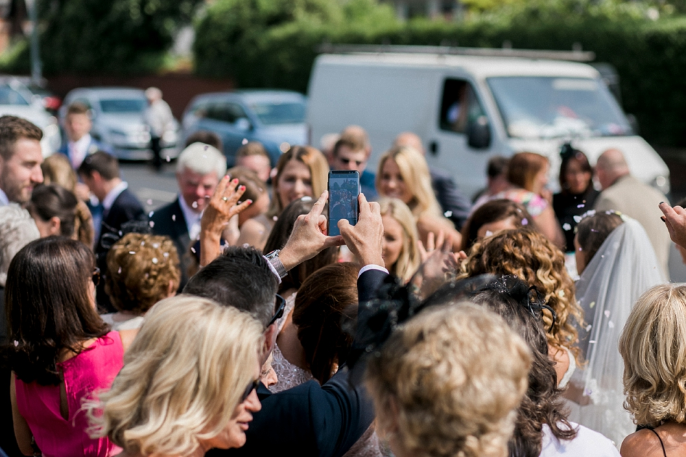 guest taking a photo with phone amongst wedding crowd