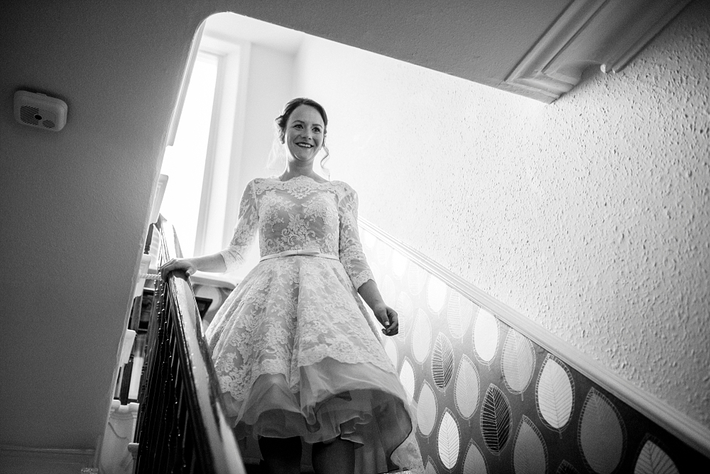 bride walks down stairs at parents home