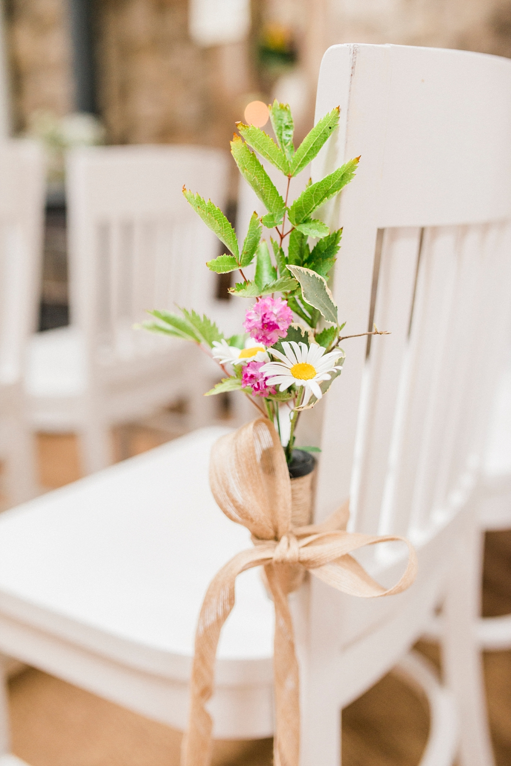 flowers on chairs at wedding ceremony