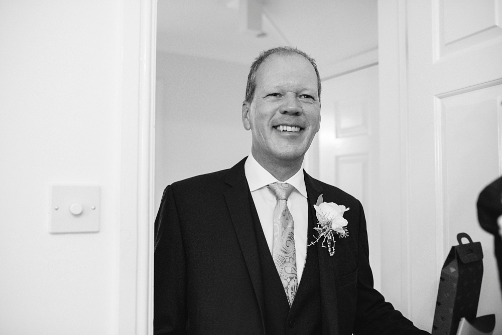 father of the bride smiles in doorway