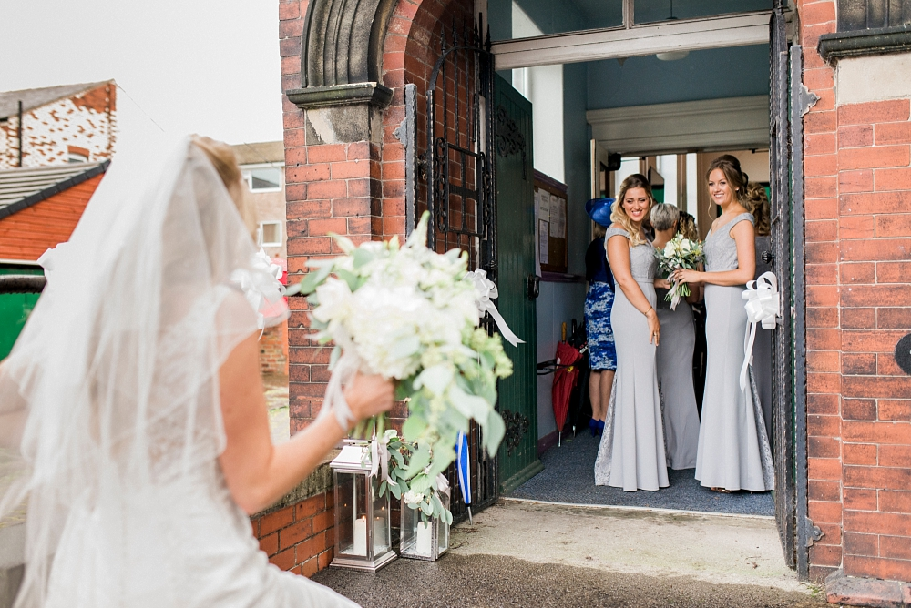 bride arrives as bridesmaids watch from church doorway