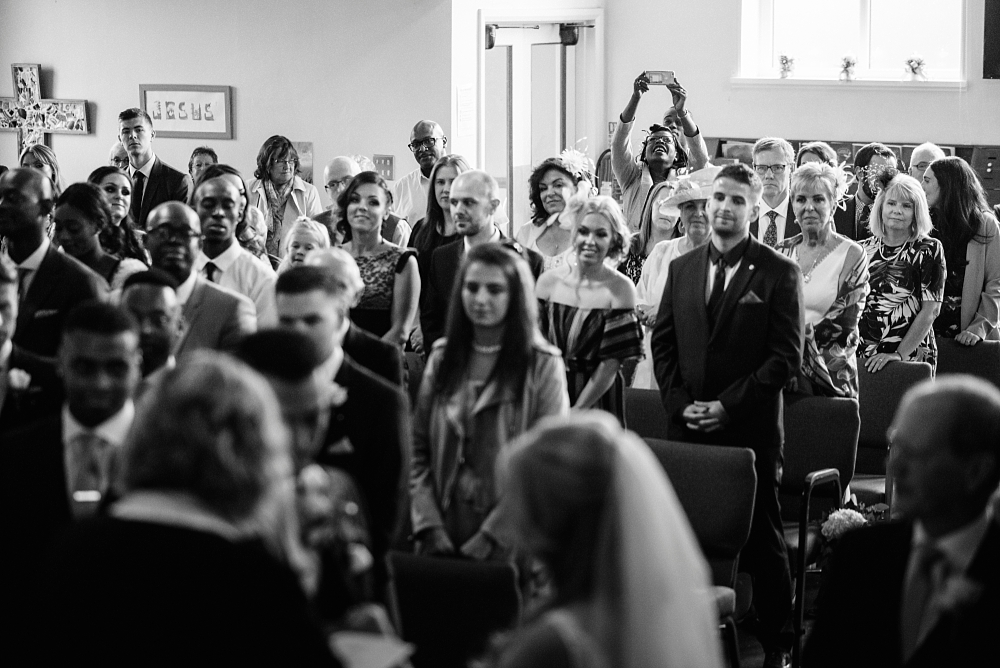 wedding guest takes photo from back of church
