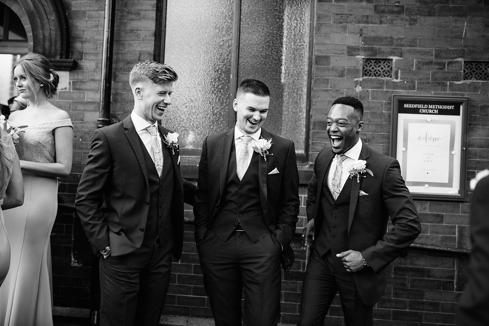 groomsmen outside church laughing