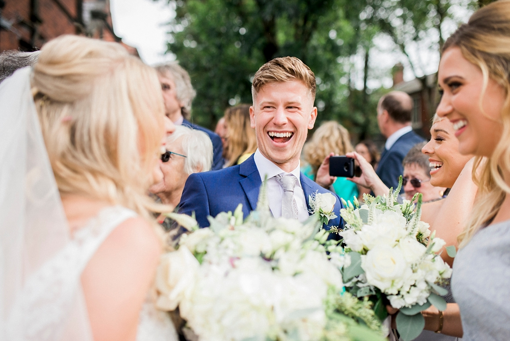 guest laughing outside church after wedding ceremony