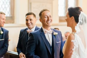 groom smiles at bride in ceremony