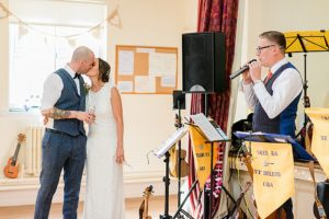 best mans speech at village hall wedding with bride and groom kissing
