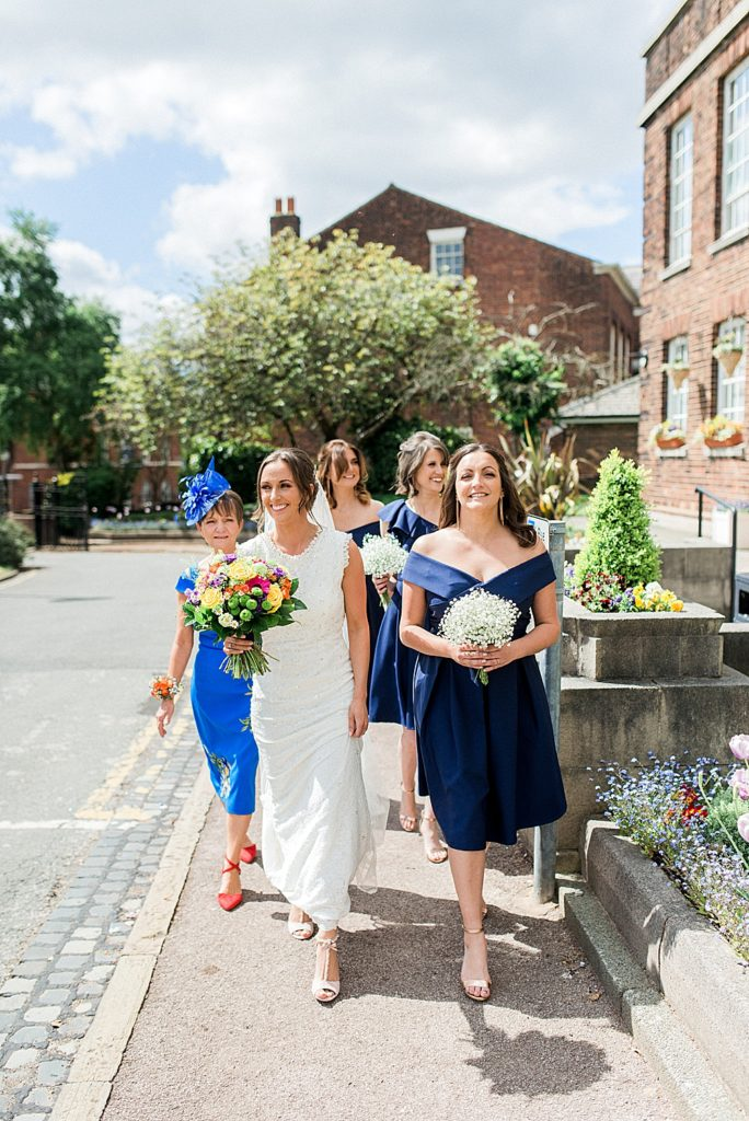 bride and her mum and bridesmaids walking into Knowsley registry office garden