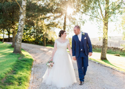 bride and groom walk in sunset at knife hall