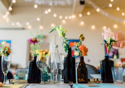 village hall wedding decor with flowers in brown bottles