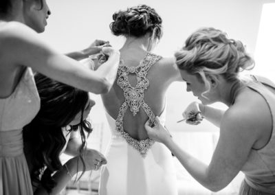 bridesmaids help bride into pronovias dress