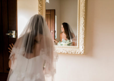 bride peeps through door in front of a mirror
