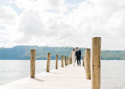 bride and groom on jetty at lake Windermere