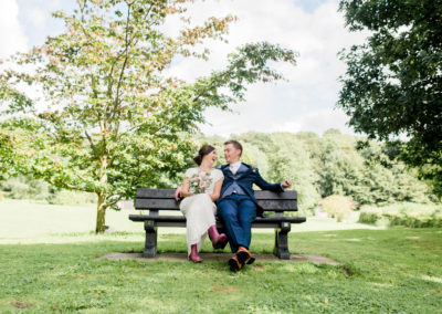 bride and groom sit on bench
