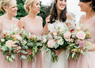 bridesmaids holding bouquets with pink flowers