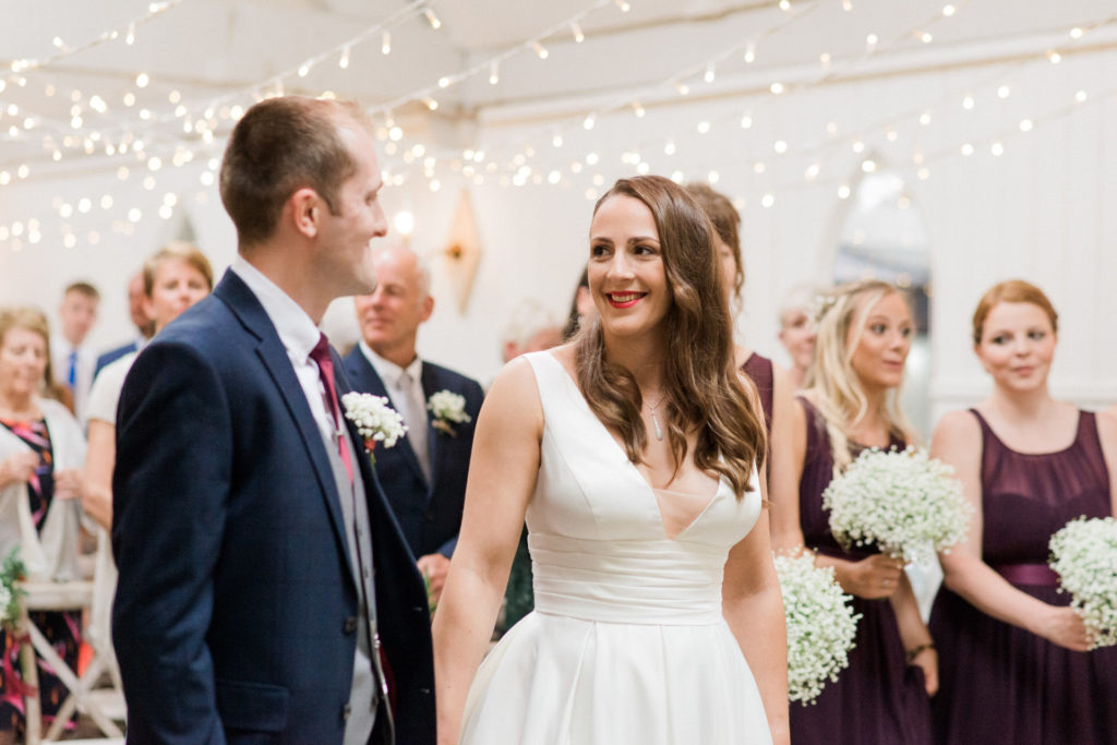 bride and groom at ceremony with fairy lights