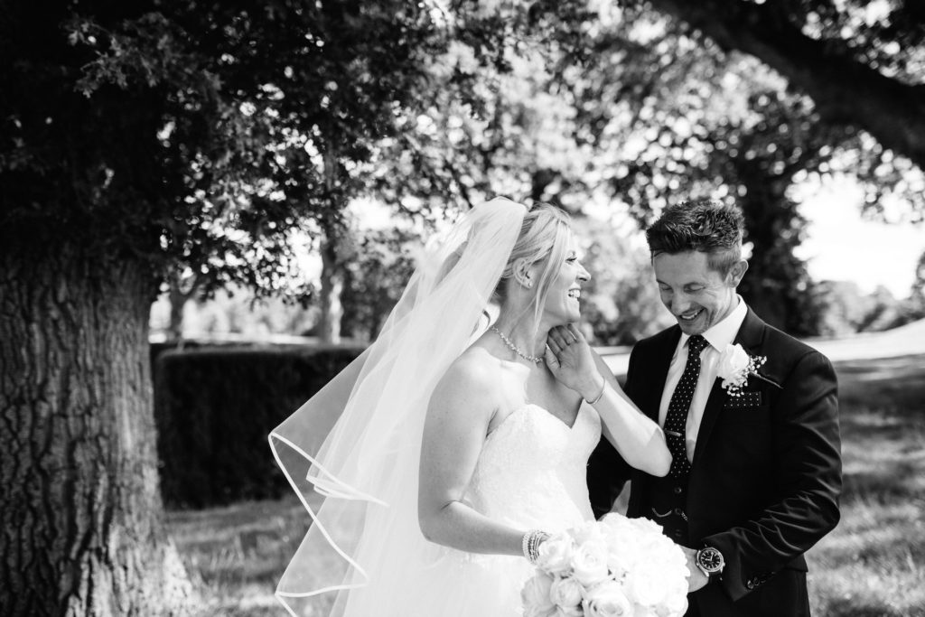 bride and groom under trees at the mere resort in knutsford