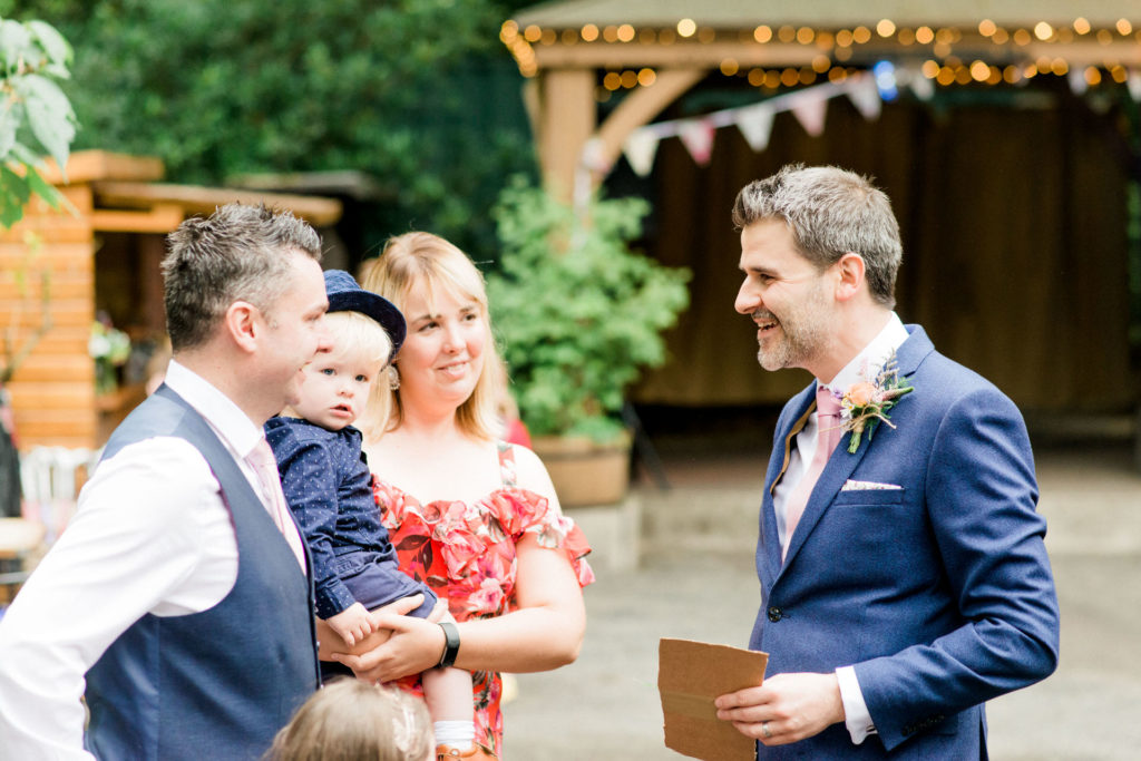 groom chats to guests at outdoor wedding