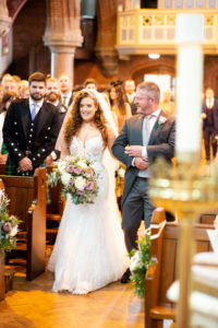 bride with ginger curly hair with her dad walking down the aisle at church