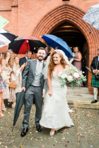 bride with red curly hair and her new husband at church