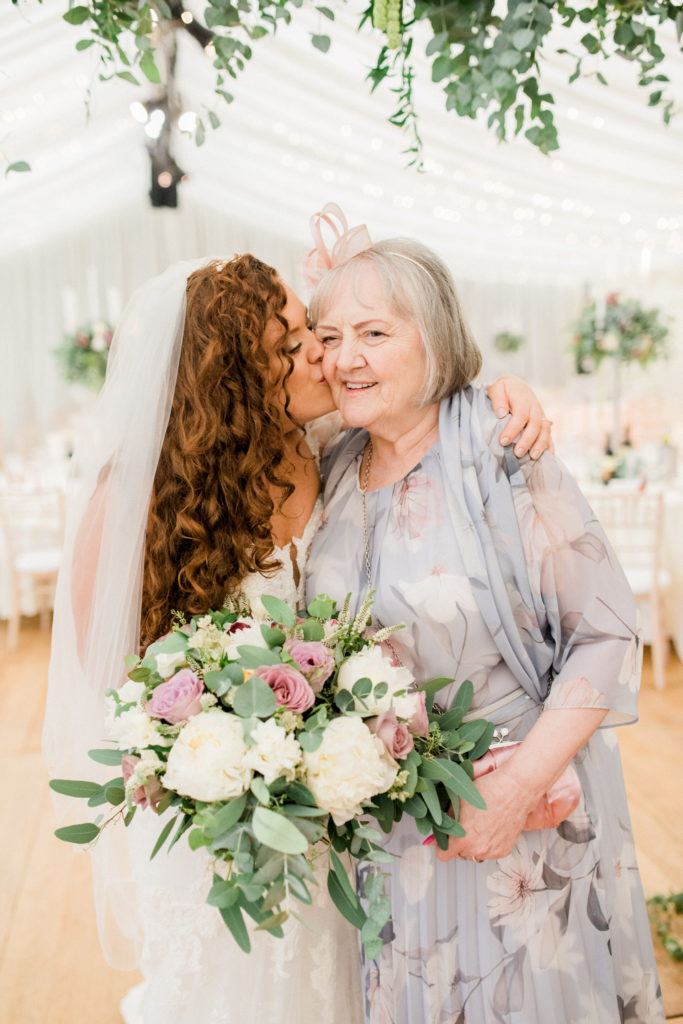 bride with long, curly, ginger hair kisses grandma on the cheek