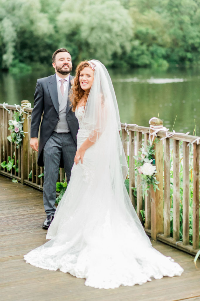 bride with ginger hair with her new husband by lake
