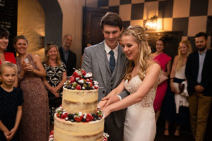 bride and groom cut cake decorated with berries