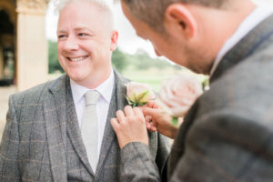 groom fixing best mans button hole
