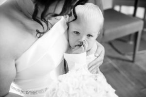 bride cuddling baby as he sheds a tear