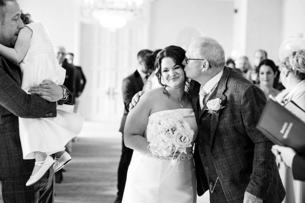 father of the bride kisses daughter at top of the aisle