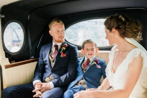 bride and groom with their little boy in wedding car