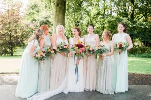 bride and bridesmaids with colourful bouquets and pastel dresses
